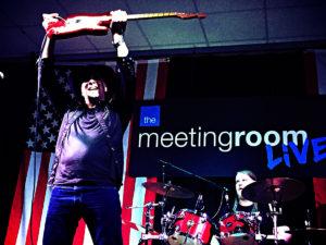 Paul Lamb with his guitar in the air